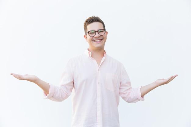 Gelukkig vreugdevolle man in brillen presenteren kopie ruimte