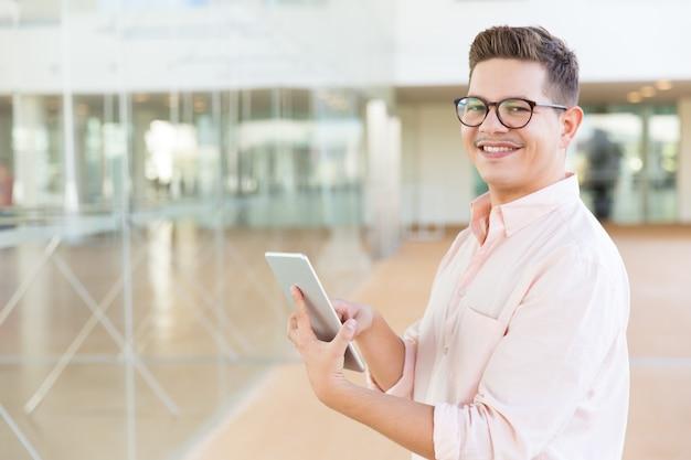 Gelukkig vreugdevolle man in glazen tablet houden