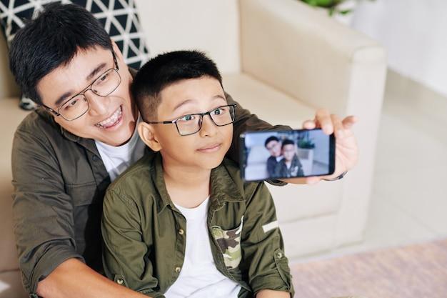 Gelukkig vreugdevolle vietnamese vader en zoon selfie te nemen op smartphone of video voor blog filmen