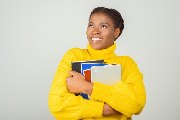 Gelukkig vreugdevolle vrouwelijke student omarmen boeken