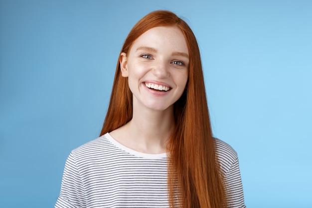 Gelukkig vriendelijke charismatische vrolijke jonge oprechte 20s roodharige meisje plezier glimlachend vrolijk lachen grapje praten terloops grijnzende camera express positieve gelukkige houding, staande blauwe achtergrond.