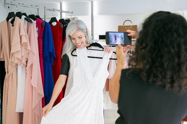 Gelukkig vriendinnen genieten van winkelen in kledingwinkel samen, jurk houden, poseren en fotograferen op mobiele telefoon. consumentisme of winkelconcept