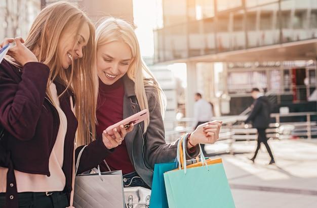 Gelukkig vriendinnen met boodschappentassen met smartphone in de stad