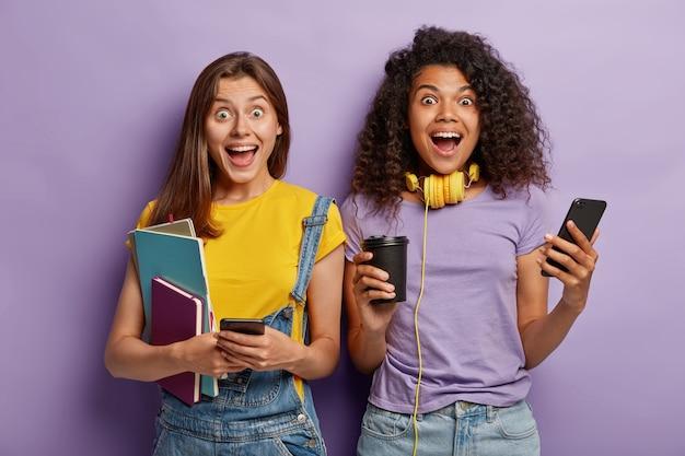 Gelukkig vriendinnen poseren met hun telefoons