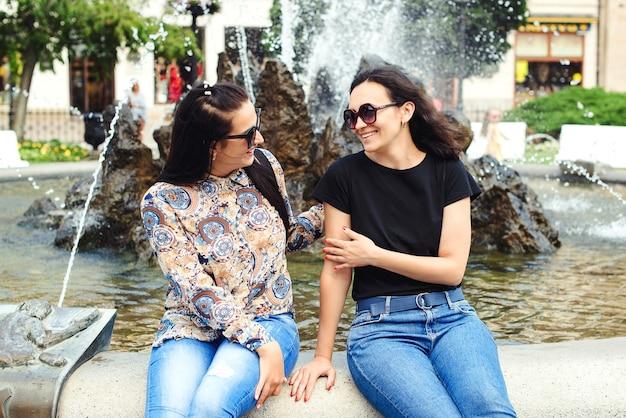Gelukkig vriendinnen praten en lachen buiten. blije jonge vrouwen die lol hebben, mooie momenten, beste vrienden.