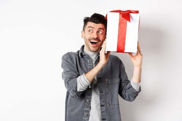 Gelukkig vriendje schudt zijn geschenk om te raden wat erin zit, ontvangt een verrassingscadeau op valentijnsdag, glimlachend en vrolijk opzij kijkend, staande op wit.