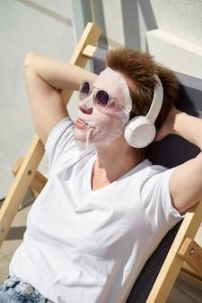Gelukkig vrij jong meisje met weefselmasker op gezichtszitting op het balkon en het luisteren aan muziek op hoofdtelefoons.