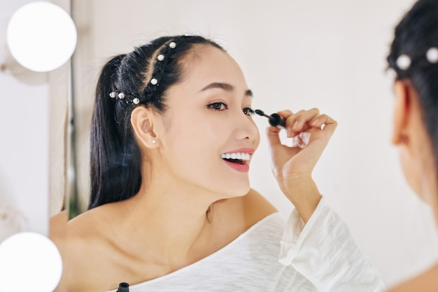 Gelukkig vrij jonge vietnamese vrouw mascara toe te passen bij het klaarmaken voor feest