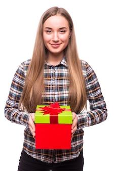 Gelukkig vrij jonge vrouw met geschenkdoos over witte muur