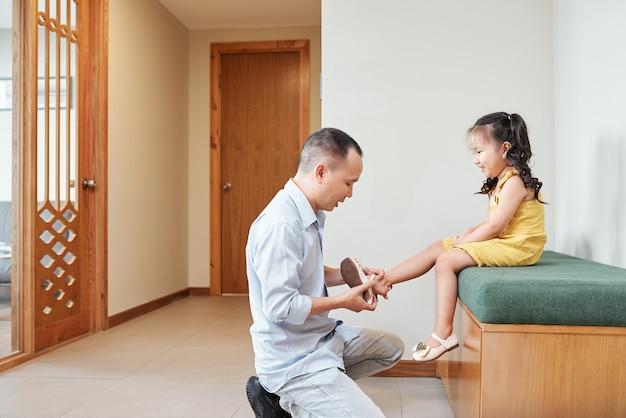 Gelukkig vrij klein aziatisch meisje dat vader haar schoenen laat aantrekken voordat ze gaan wandelen