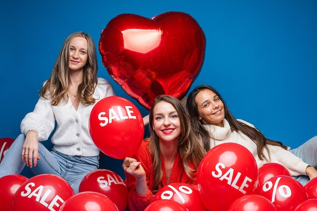 Gelukkig vrij vriendinnen zitten met verkoop rode lucht ballonnen, geïsoleerd op blauwe muur