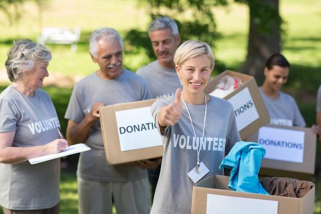 Gelukkig vrijwilligersblonde met duim omhoog