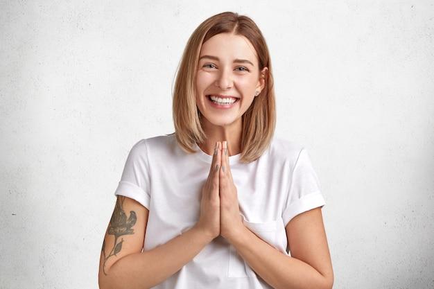 Gelukkig vrolijk aangenaam uitziende vrouw pleit voor iets en houdt de handpalmen tegen elkaar gedrukt, glimlacht vreugdevol, geïsoleerd over wit