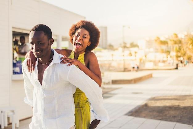 Gelukkig vrolijk, aantrekkelijk afrikaans stel met zwarte huid geniet van de vrijetijdsbesteding in de buitenlucht in de stad. de man draagt het lachende meisje op zijn rug. mooie millennials houden van en spelen samen