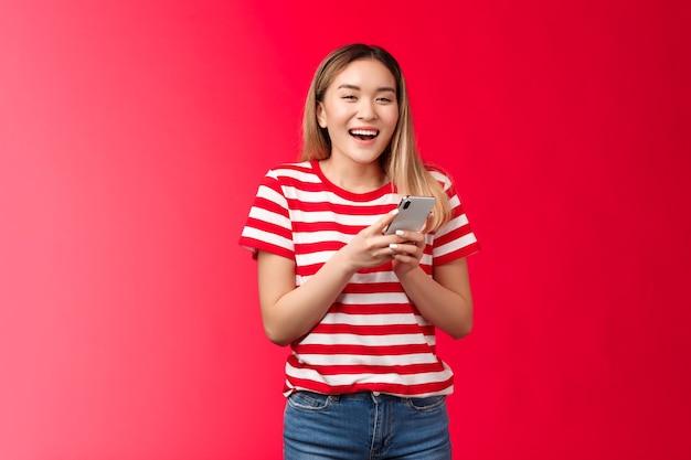 Gelukkig vrolijk aziatisch blond meisje dat lacht met behulp van smartphone meisje houdt apparaat glimlachend breed kijk kwam...