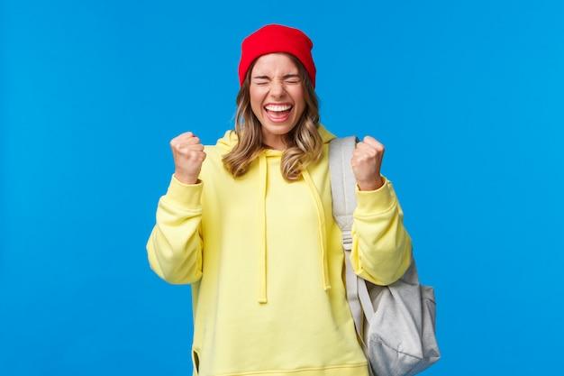 Gelukkig vrolijk blond meisje in rode muts en gele hoodie, opgeluchte ogen dicht en glimlachend zegevierend, goed nieuws gevierd, examens behaald op de universiteit, vuistpomp als kampioen, prijs gewonnen