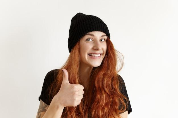 Gelukkig vrolijk europees meisje met tatoeage en rommelig kapsel, met thumbs-up gebaar