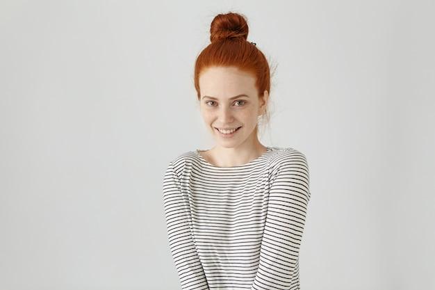 Gelukkig vrolijk europees tienermeisje met gemberhaar knoop in gestreept t-shirt met lange mouwen met een vrolijke uitstraling, een brede glimlach, genietend van een goede dag en vrije tijd binnenshuis