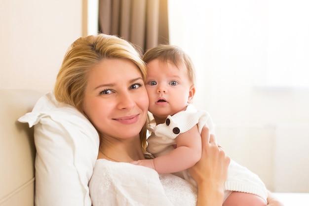 Gelukkig vrolijk familieconcept. moeder en baby van drie maanden zoenen, lachen en knuffelen, close-up portret