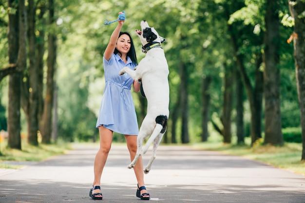 Gelukkig vrolijk glimlachend donkerbruin meisje in het blauwe de zomerkleding spelen met grote jachthond in park