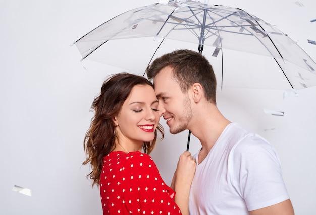 Gelukkig vrolijk jong schattig paar verliefd in modieuze elegante kleding met een paraplu