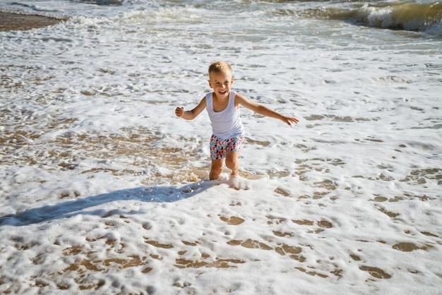 Gelukkig vrolijk jongetje loopt langs het strand in de golven op een zonnige zomerdag, concept van de familievakantie