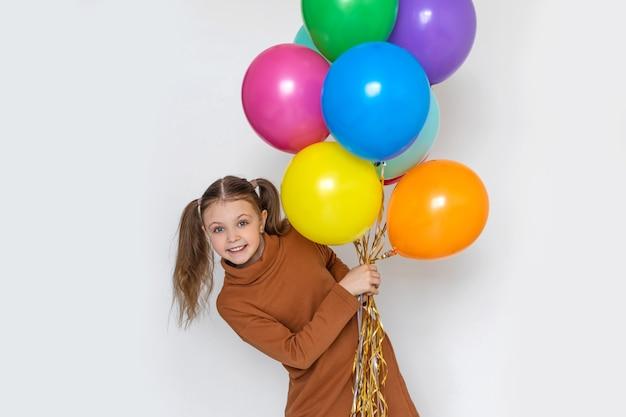 Gelukkig vrolijk meisje dat gekleurde ballen vasthoudt en vrolijk lacht