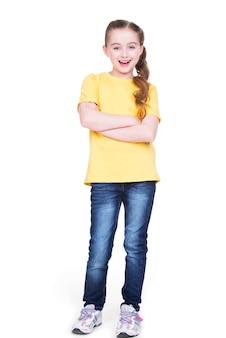 Gelukkig vrolijk meisje dat met gekruiste handen camera in volle lengte bekijkt die zich op witte achtergrond bevindt.