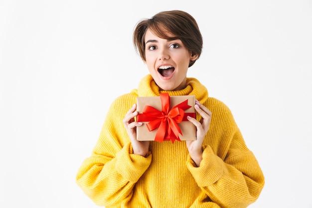 Gelukkig vrolijk meisje dragen hoodie staande geïsoleerd op wit, met geschenkdoos