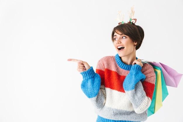 Gelukkig vrolijk meisje dragen trui staande geïsoleerd op wit, met boodschappentassen