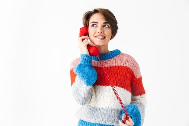 Gelukkig vrolijk meisje dragen trui staande geïsoleerd op wit, praten over een vaste telefoon