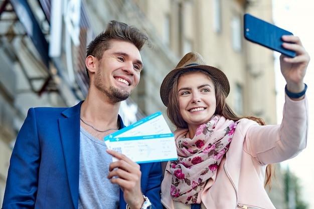 Gelukkig vrolijk paar dat en vliegende kaartjes koestert toont. man die een vrouw verrast - kaartjes geeft voor een huwelijksreis