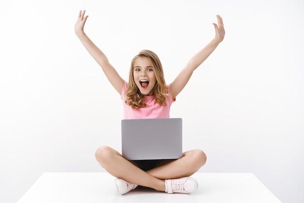 Gelukkig vrolijk schattig blond meisje dat plezier heeft zomervakantie weg van school, geniet van het kijken naar tekenfilms, zit gekruiste benen met behulp van laptop, opgewonden thuis studeren met e-learning programma