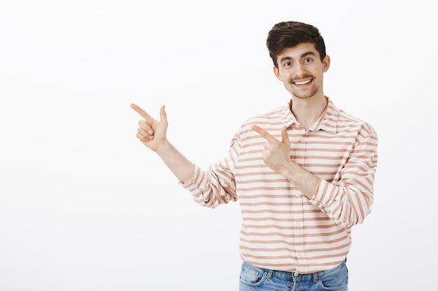 Gelukkig vrolijk volwassen bebaarde mannelijk model met tevreden vriendelijke uitdrukking, wijzend met vingerpistolen in de linkerbovenhoek, glimlachend terwijl vriend haar mening vraagt over grijze muur