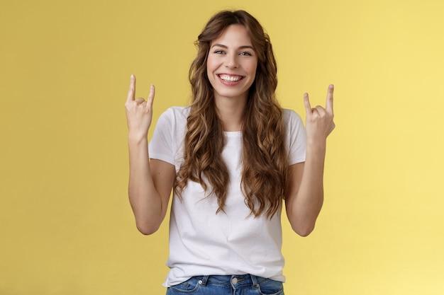 Gelukkig vrolijk vrouwelijk kaukasisch meisje krullend kapsel toon rock-n-roll heavy metal gebaar glimlachend in het algemeen genieten van geweldige concertsfeer staan gele achtergrond vreugdevol juichen tevreden