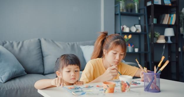 Gelukkig vrolijke aziatische familie moeder leert peuter meisje verf keramische pot plezier ontspannen op tafel in de woonkamer thuis
