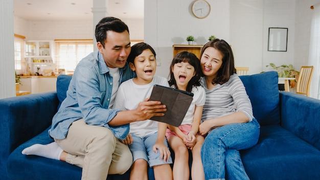 Gelukkig vrolijke aziatische familie vader, moeder en kinderen die plezier hebben en digitale tablet video-oproep gebruiken op de bank thuis.
