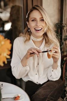 Gelukkig vrolijke blonde vrouw in stijlvolle witte blouse en donkere fluwelen broek lacht, kijkt in de camera en smeert plakken op stuk brood in straatcafé