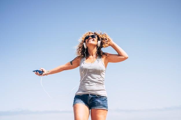 Gelukkig vrolijke dame met blond krullend haar luisteren muziek met koptelefoon en mobiele telefoon buiten met plezier en genieten van het leven