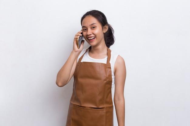 Gelukkig vrolijke jonge aziatische vrouw barman of serveerster met behulp van mobiele smartphone op witte achtergrond