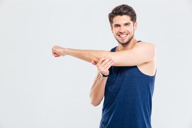 Gelukkig vrolijke jonge sportman doet rekoefeningen geïsoleerd op een grijze achtergrond
