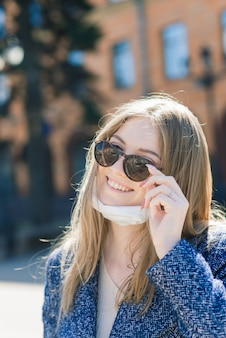 Gelukkig vrolijke jonge vrouw medische gezichtsmasker verwijderen terwijl staande op straat in de stad.