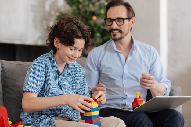Gelukkig vrolijke jongen zittend op de bank naast zijn vader en het monteren van een toren met blok set terwijl zijn vader met hem praat