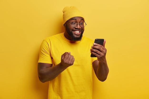 Gelukkig vrolijke man balde vuist met triomf, horloges voetbalwedstrijd online, gericht op smartphoneapparaat, draagt ronde bril