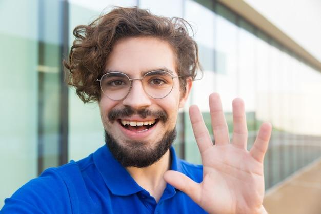 Gelukkig vrolijke man draagt een bril, hallo zwaaien