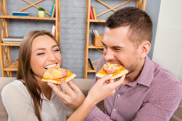 Gelukkig vrolijke man en vrouw elkaar voeden met pizza