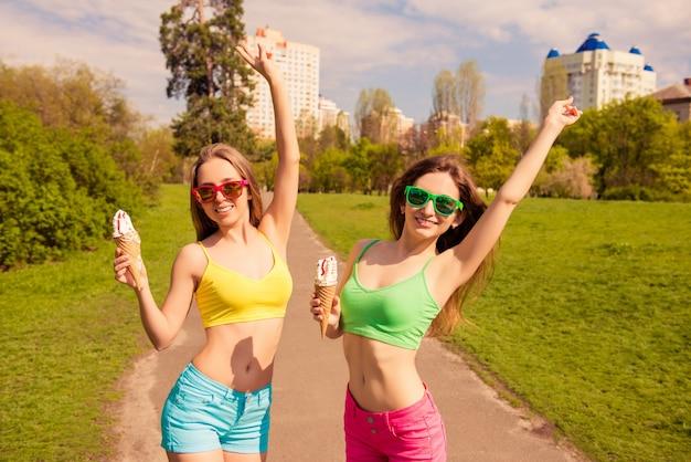 Gelukkig vrolijke meisjes wandelen in het park met ijs en opgeheven handen