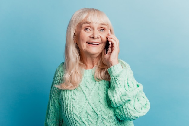 Gelukkig vrolijke volwassen vrouw praten op smartphone geïsoleerd op blauwe achtergrond