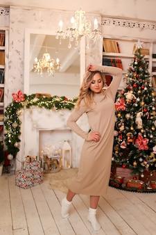 Gelukkig vrolijke vrouw in een comfortabele thuisjurk en sokken poseren in een feestelijk interieur in de buurt van de boom