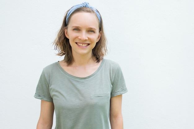 Gelukkig vrolijke vrouw in haarband en t-shirt camera kijken